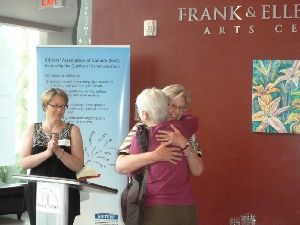 Perry Millar receives a hug after being named an Honorary Life Member of Editors Canada